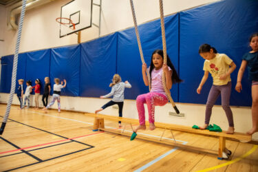 Primary School students swinging on ropes in the gym