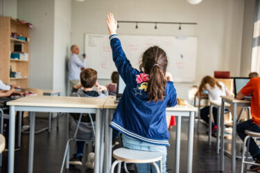A girl with her hand up in class