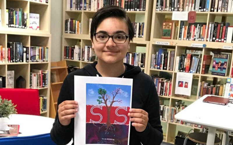 Student with winning year book cover
