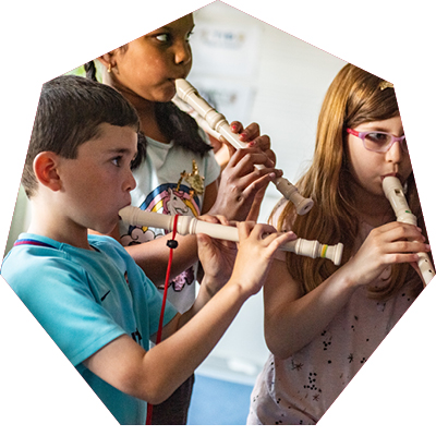 Three small children playing the recorder